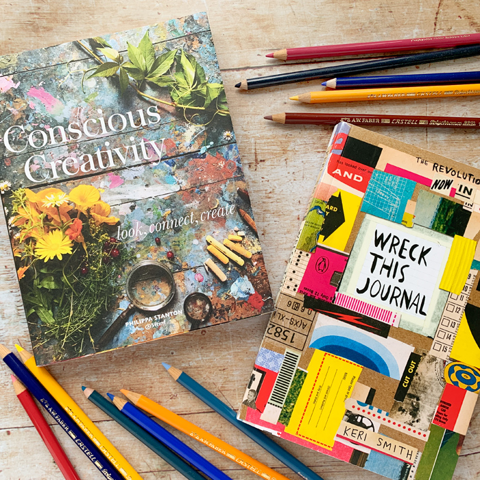Wreck This Journal and Conscious Creativity books on a wooden table surrounded by coloured pencils